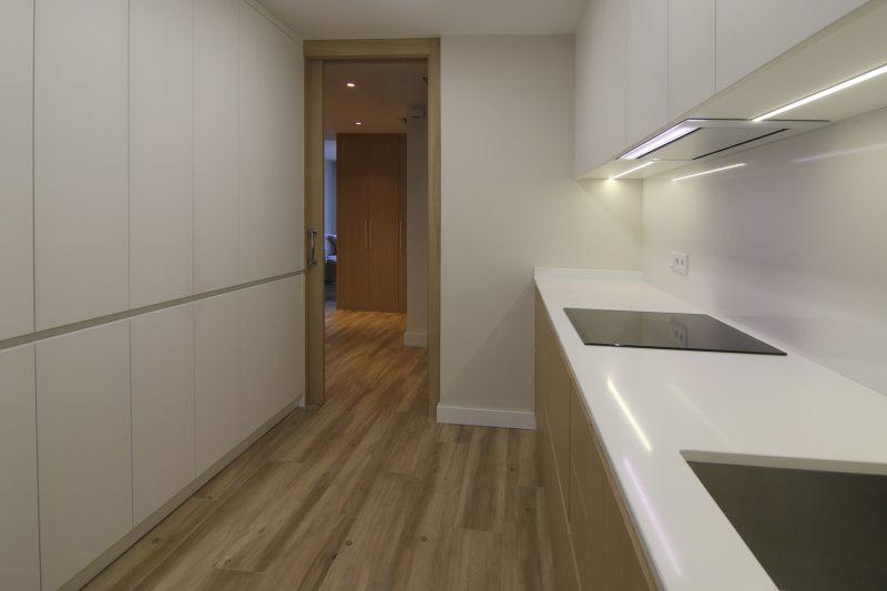 Cocina con muebles rectos y lisos. Apertura con uñeros y entrada a través de puerta corredera.